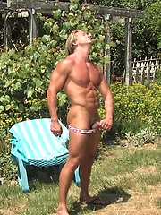 Handsome muscled man showing his strong naked body under sun